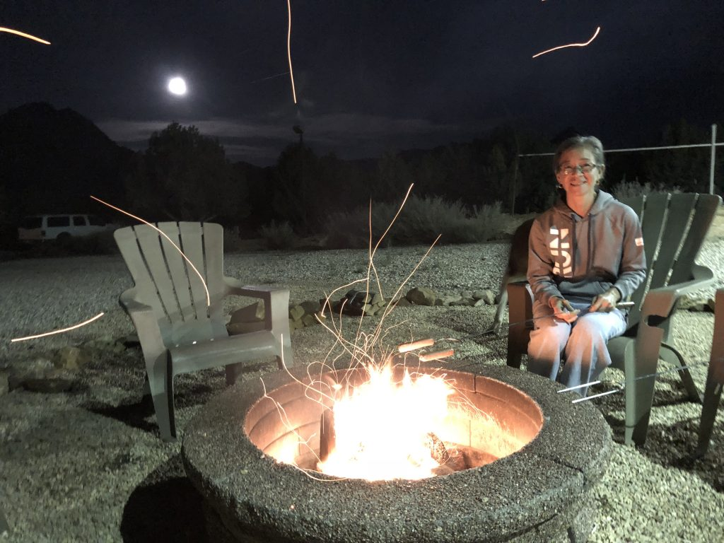 Person roasting hot dogs in a fire pit