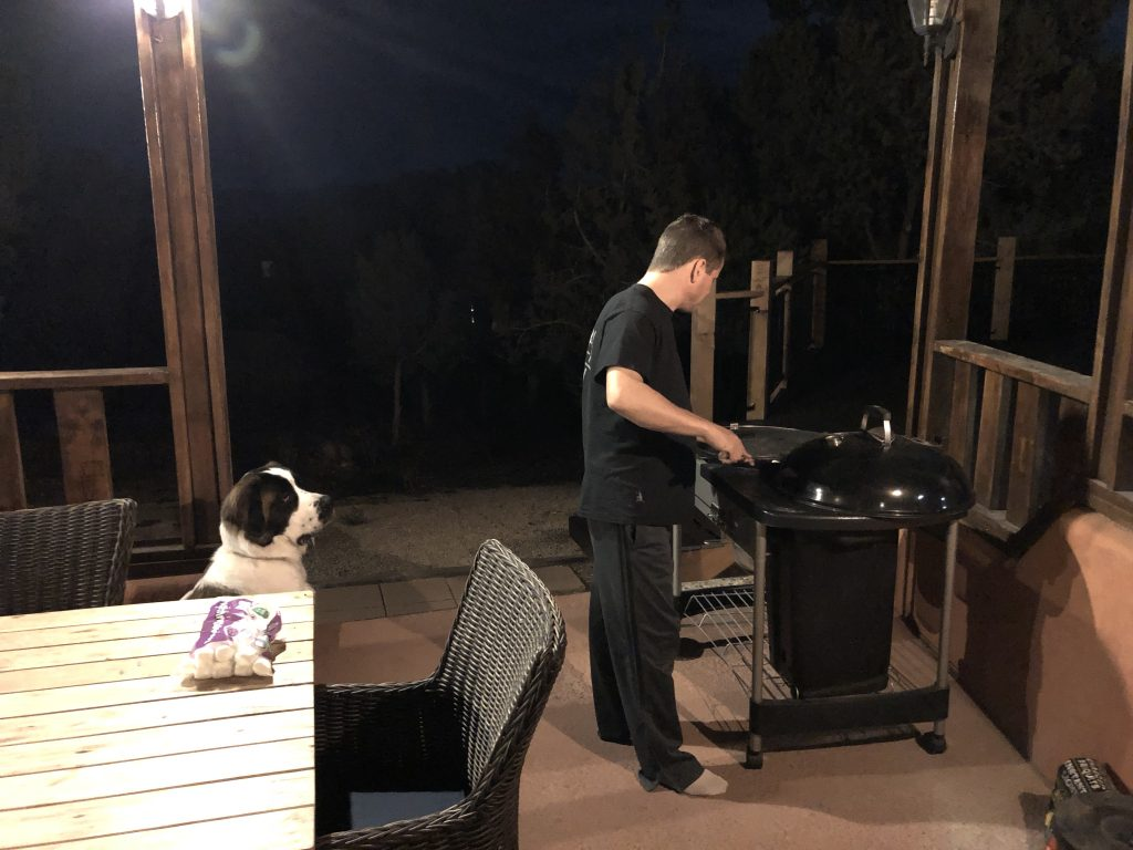 Person grilling steaks with dog watching