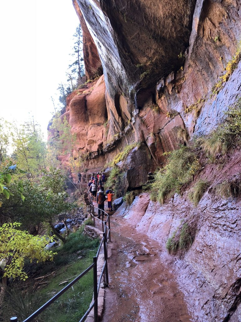 People on trail with cliffs at Zion National Park