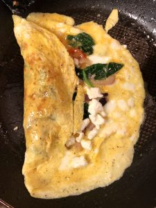 Omelette with spinach, feta, cherry tomatoes and red onions folded over