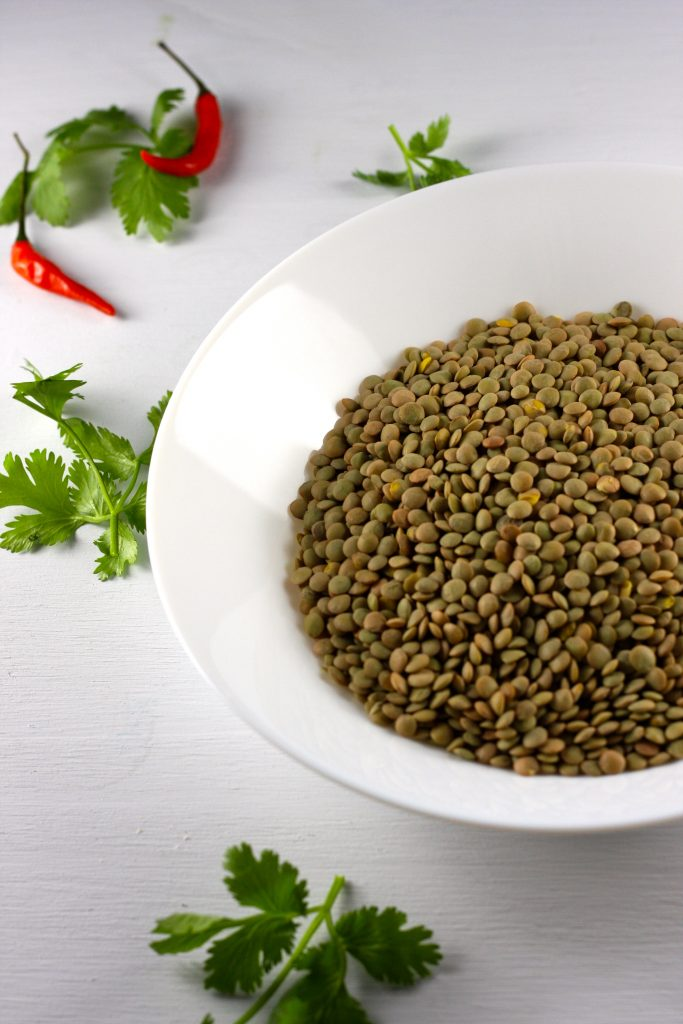 Green lentils in a bowl surrounded by cilantro and chili