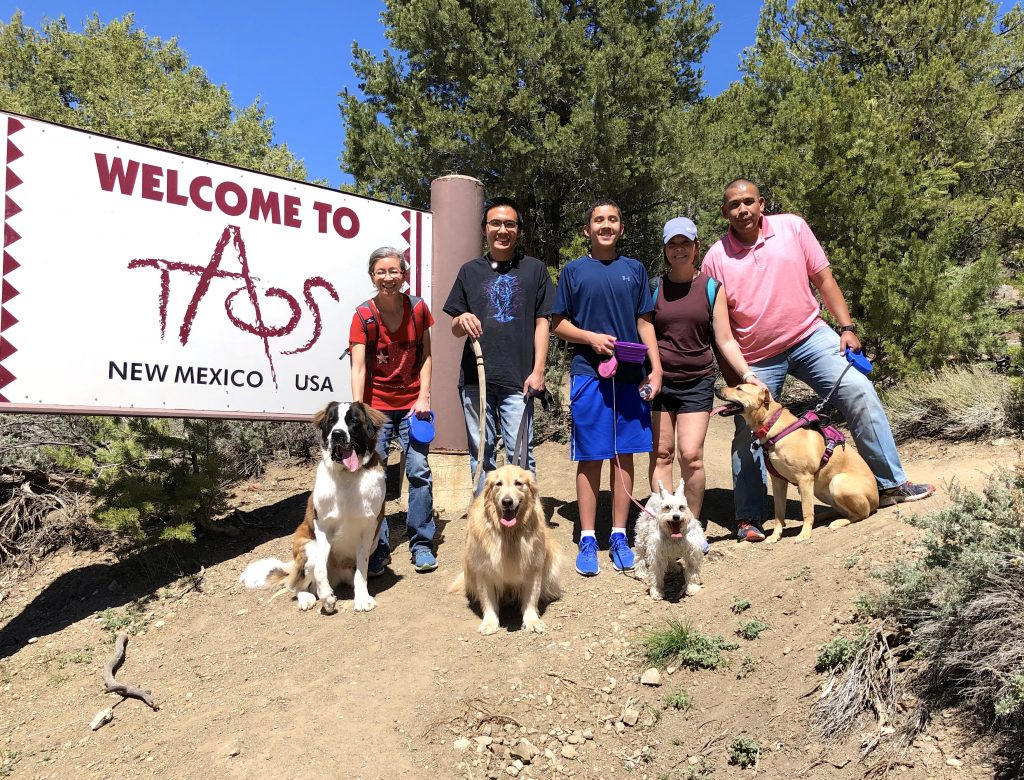 People and dogs by Welcome to Taos Sign