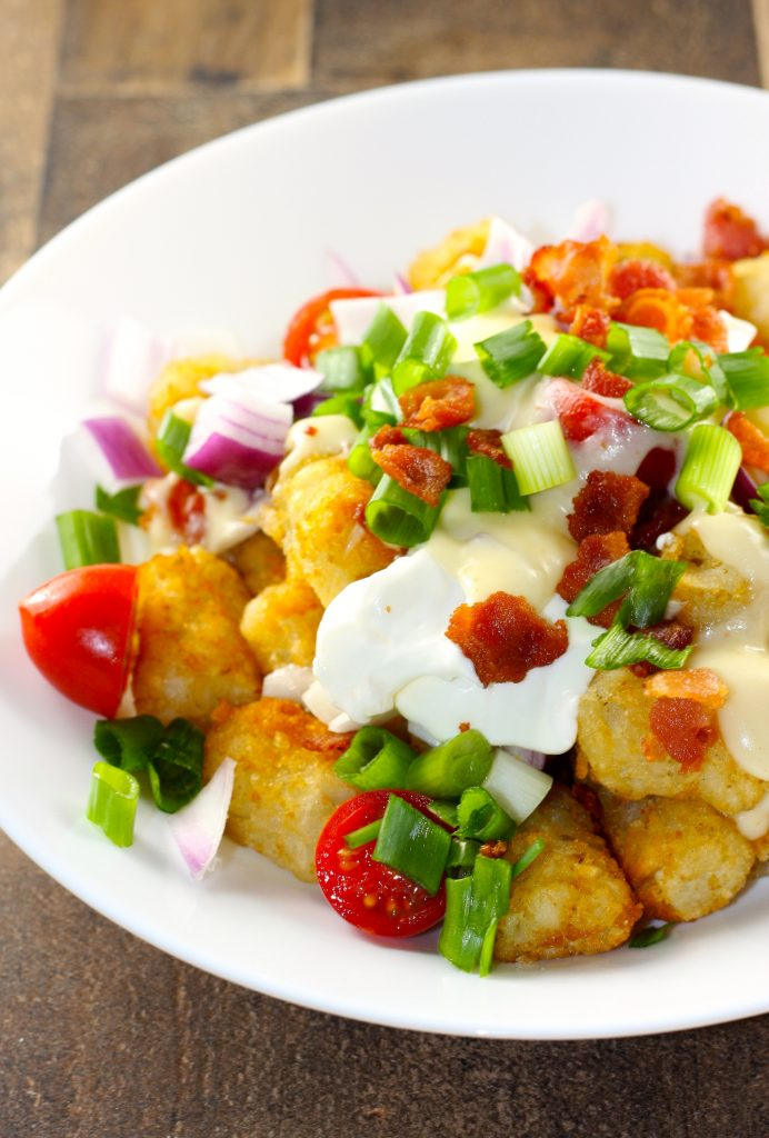 Tots bacon sour cream tomatoes green onions red onions cheese sauce