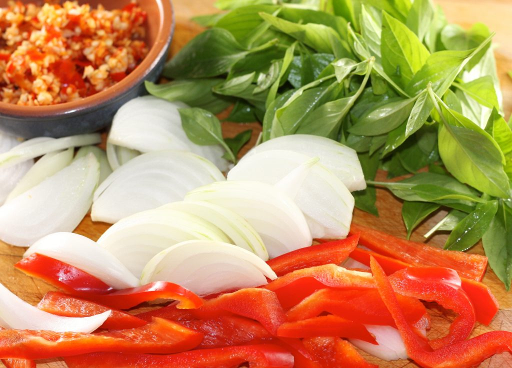Thai Basil, Onions, Red Pepper, garlic and chilis minced in a bowl