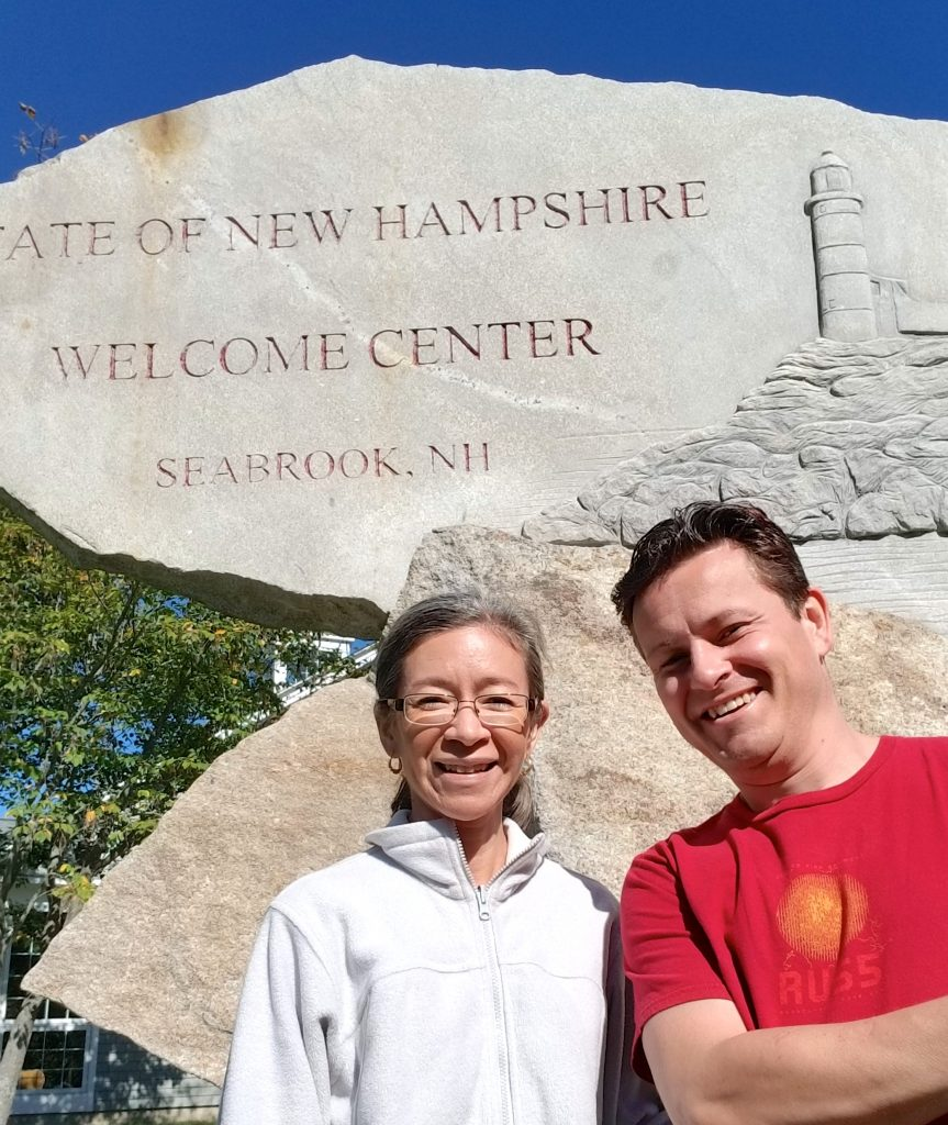State of New Hampshire Welcome Center Sign with People