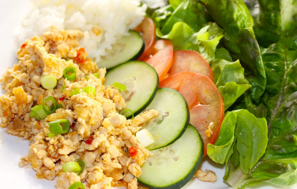 Asian chicken lettuce wrap with rice cucumber and tomatoes
