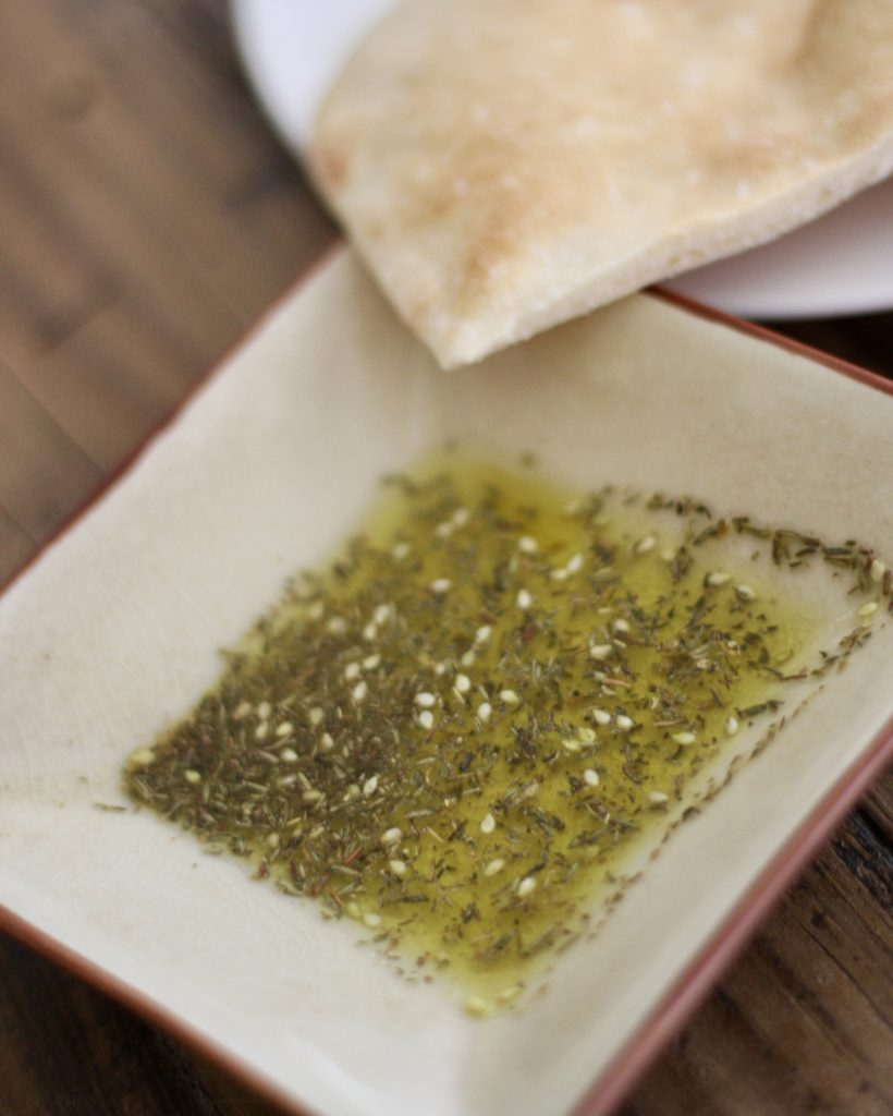 za'atar mixed with olive oil in a dish and pita bread on the side