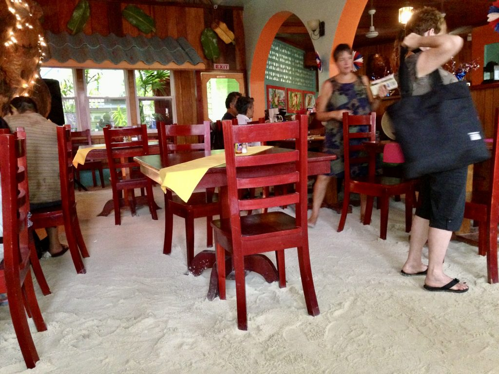 Interior of Elvi's Kitchen restaurant with dining tables and a sand floor
