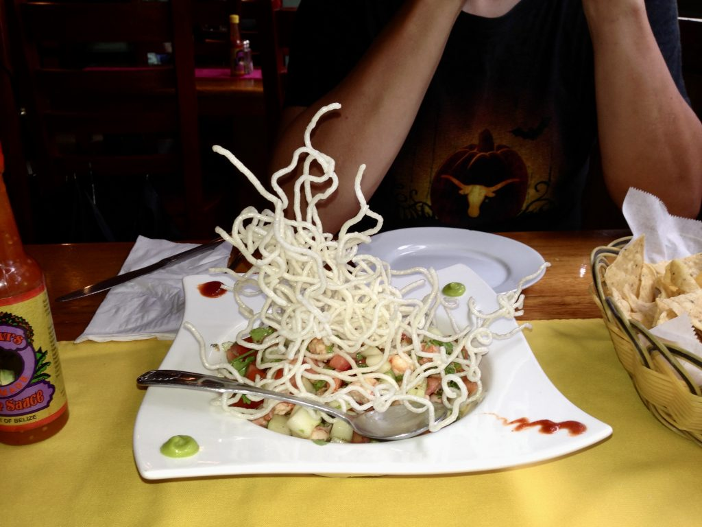 Wasaviche from Elvi's kitchen ceviche topped with fried noodles on a white plate