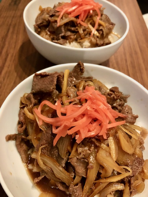 Gyudon on rice topped with pickled ginger in a bowl