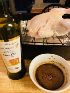Olive oil, basting sauce and chicken on a roasting pan