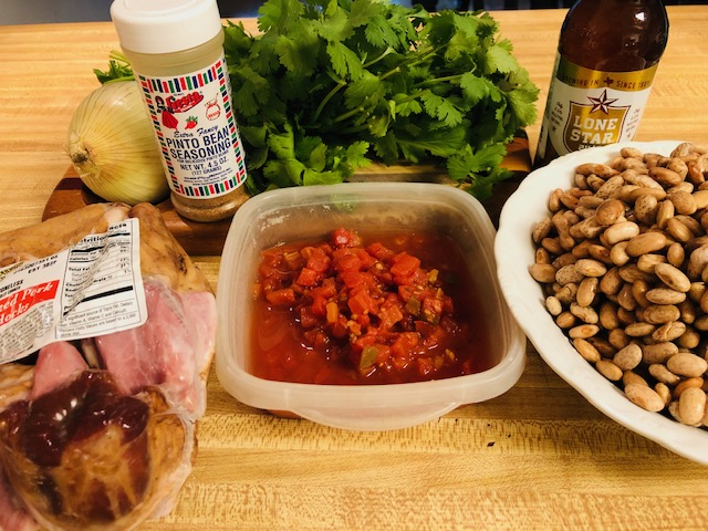 Pork hock, pinto beans, onion, pinto bean seasoning, diced tomatoes, cilantro, lone star beer