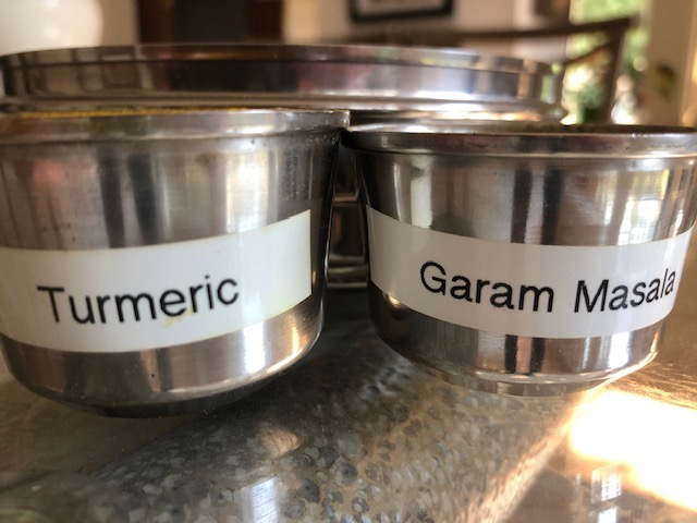 spice pots labeled turmeric and garam masala