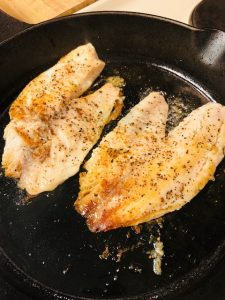 Browned tilapia fillets in a pan