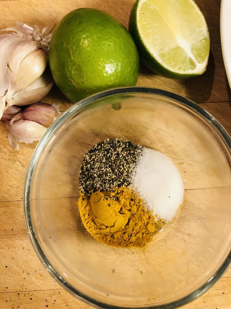 spice mix of turmeric, salt, and pepper;  garlic and limes