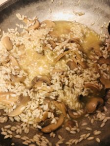 arborio rice, mushrooms, and broth in a skillet