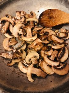 diced mushrooms in a skillet with a wooden spoon