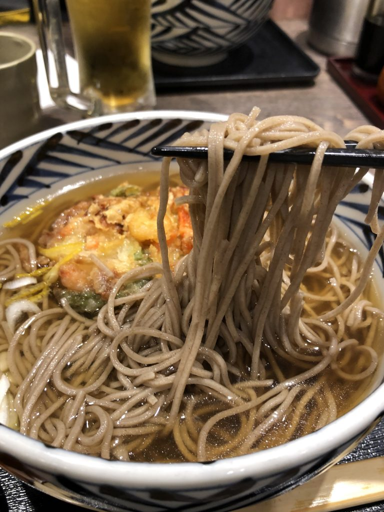 soba noodles in a bowl with chopsticks and tempura