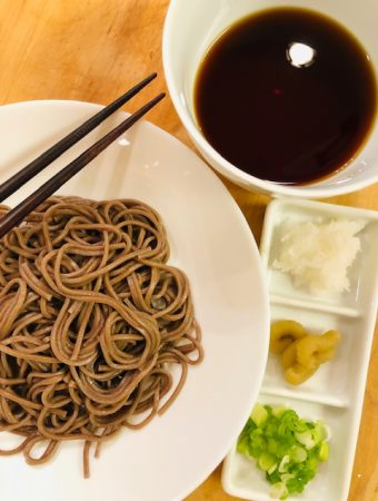 soba noodles in a white bowl with chopsticks, white bowl with soba sauce, and daikon, wasabi, and scallions on a white serving tray