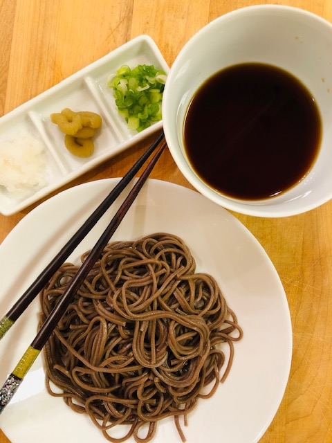 Soba noodles in a bowl, soba sauce in a bowl, and green onions, wasabi, grated daikon and chopsticks