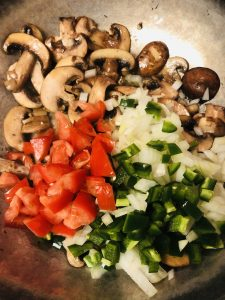 sliced mushrooms, diced tomato, diced onion, diced jalapeno in a skillet