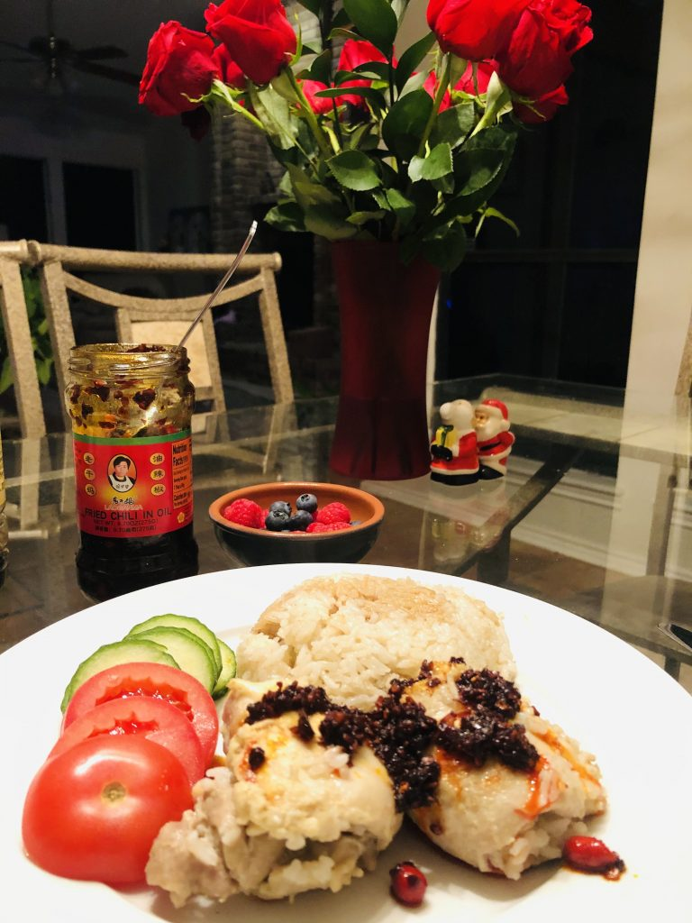Hainanese Chicken Rice, chili oil, fruit, santa and mrs klaus, and a vase of red roses
