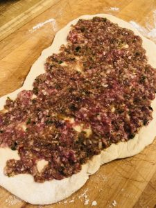 lamb mixture on top of a flatbread dough