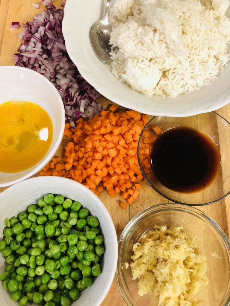 Rice in a bowl, chopped up onion and carrots, minced garlic and ginger, peas and soy sauce