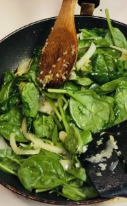Spinach, onions and garlic in a nonstick pan with a wooden spoon