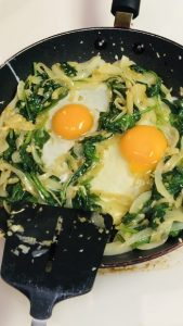Eggs set into spinach mixture in a nonstick pan