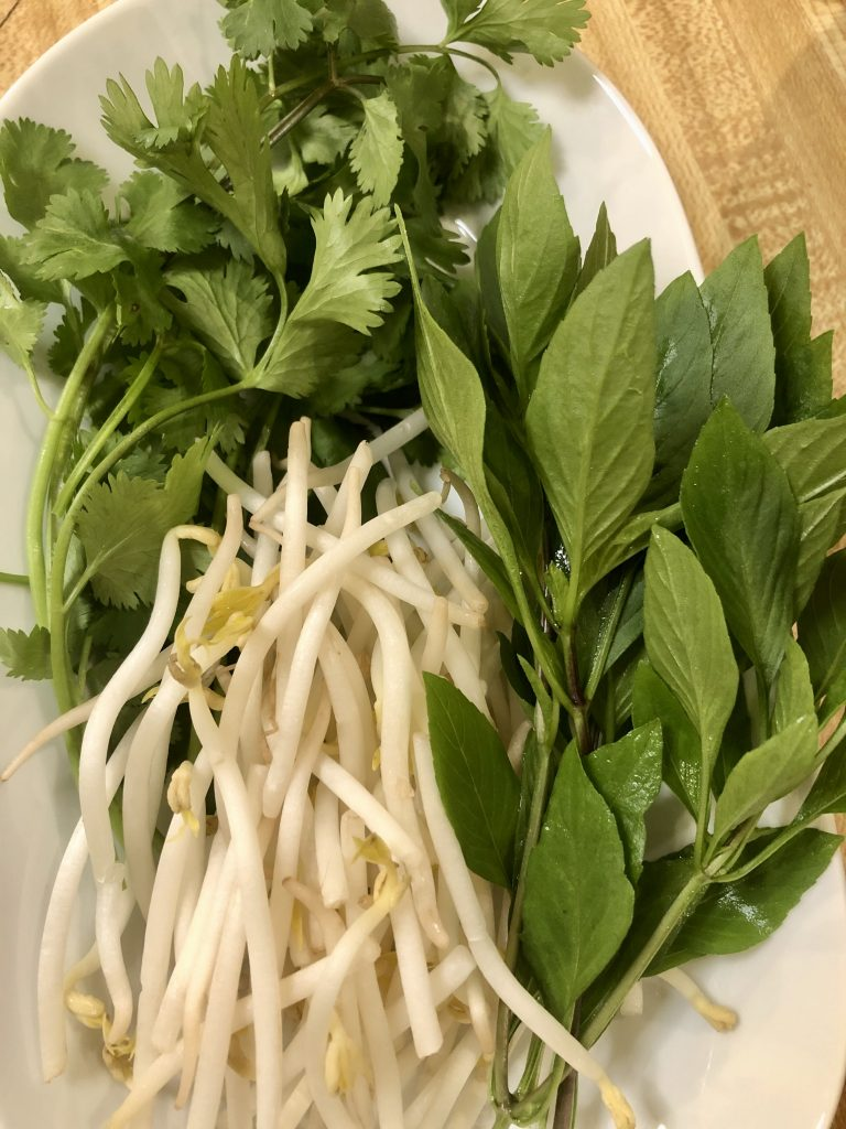 Bean sprouts, cilantro, and Thai basil in a white dish