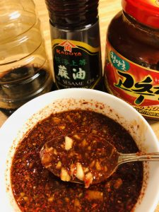 gochujang, sesame oil, soy sauce, and spicy sauce in a white bowl