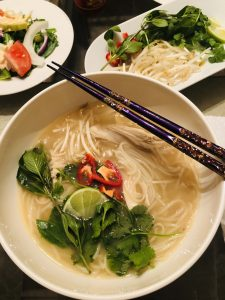 Pho Ga in a bowl with chopsticks and garnished with fresh herbs