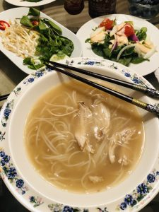 Pho ga in a bowl with chopsticks, a salad, and garnishes