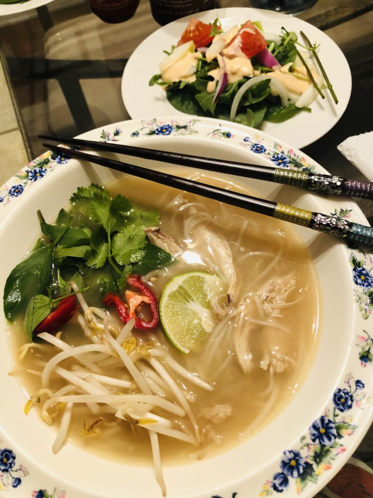 Pho Ga in a bowl with chopsticks and salad