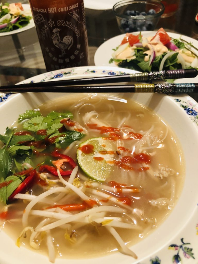 Pho Ga with sriracha and chopsticks and salad