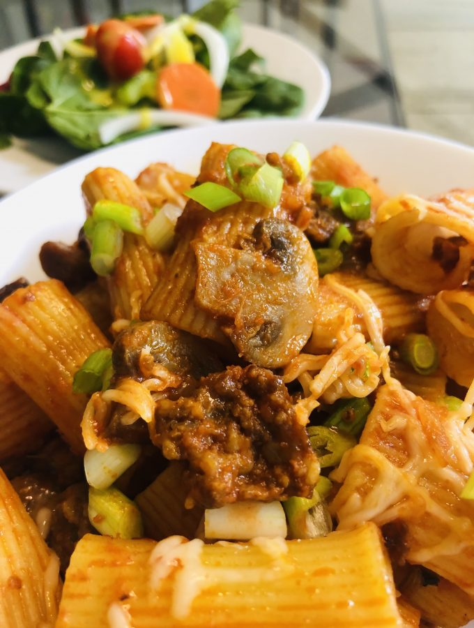 Rigatoni With Sausage in a white bowl with salad in the background