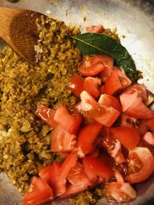 onion and spice mixture with diced tomatoes, bay leaf, and a wooden spoon