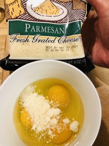 Eggs and parmesan cheese in a white bowl, with a packet of parmesan cheese