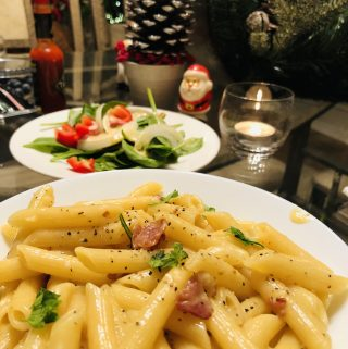Penne Carbonara with salad, santa claus, tabasco bottle, greenery, and a lit candle in the background