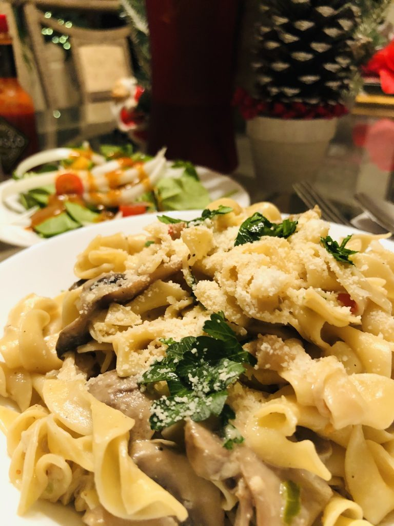 Creamy Chicken and Mushroom Pasta with salad in the background