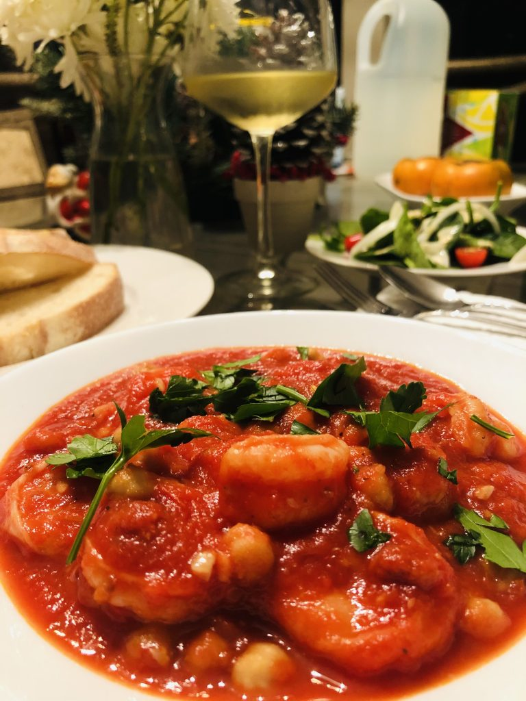 Shrimp and Chorizo Stew with wine, bread, and salad in the background