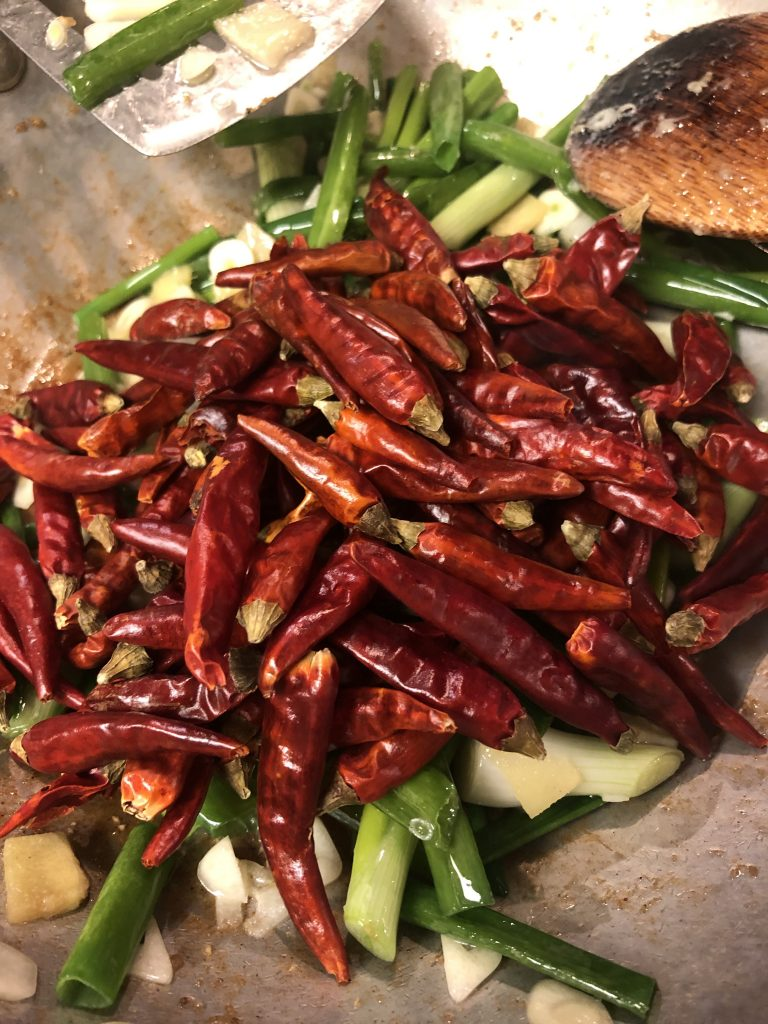 ginger, garlic, scallions and chilies in a large skillet