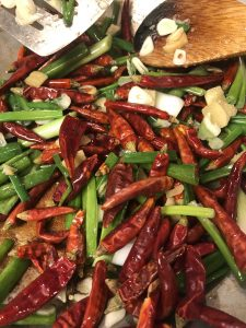 Garlic, ginger, chilies, and scallions in a skillet with a wooden spoon