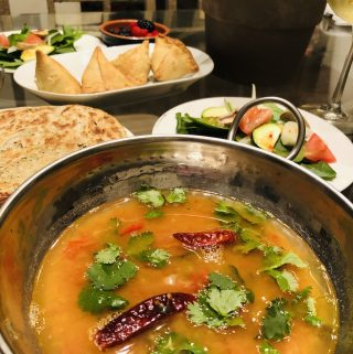 Khatti Daal with salad, paratha, and samosas in the background
