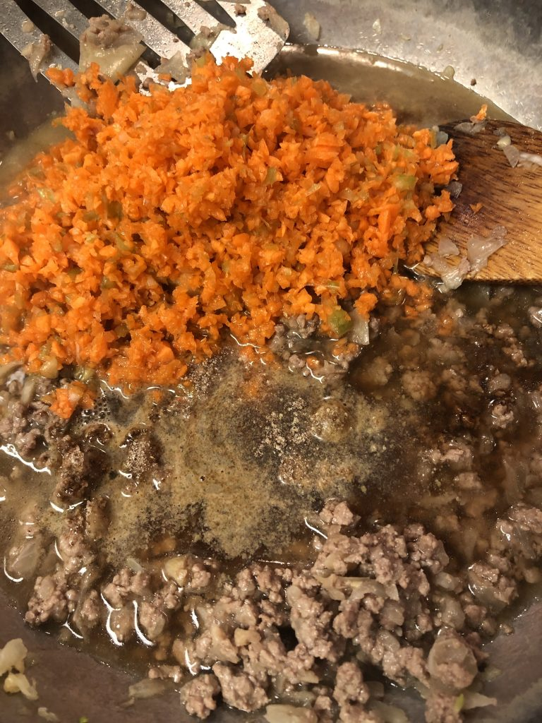 browned mince beef, and chopped carrot and celery in a pan, with beef stock and beef bouillon