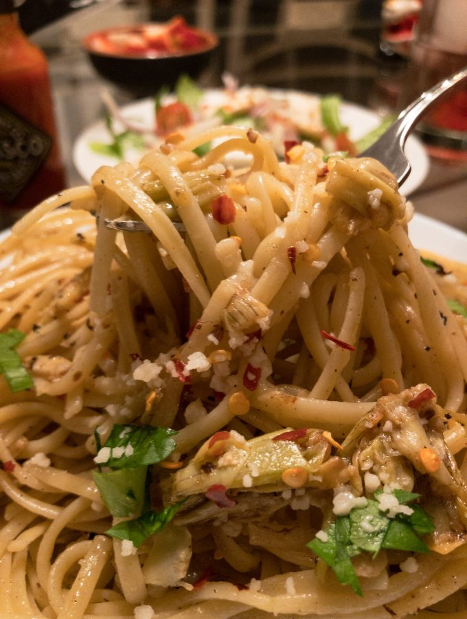 Artichoke Pasta held up by a fork with salad and Tabasco sauce in the background