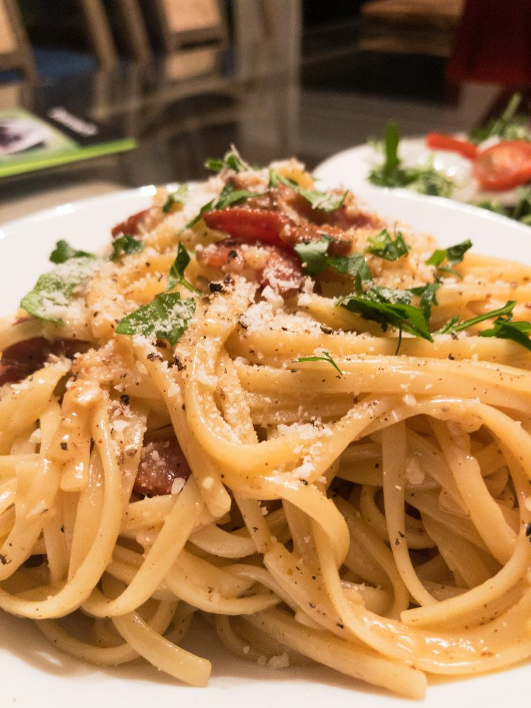 Spaghetti Carbonara on a white plate with salad in the background
