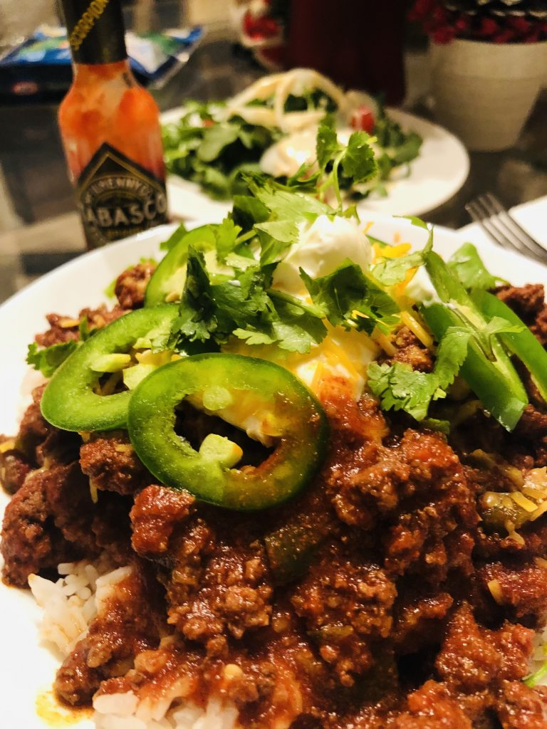 Texas Chili with sliced jalapenos, sour cream, cilantro, and cheese with a Tabasco bottle and salad in the background served with rice