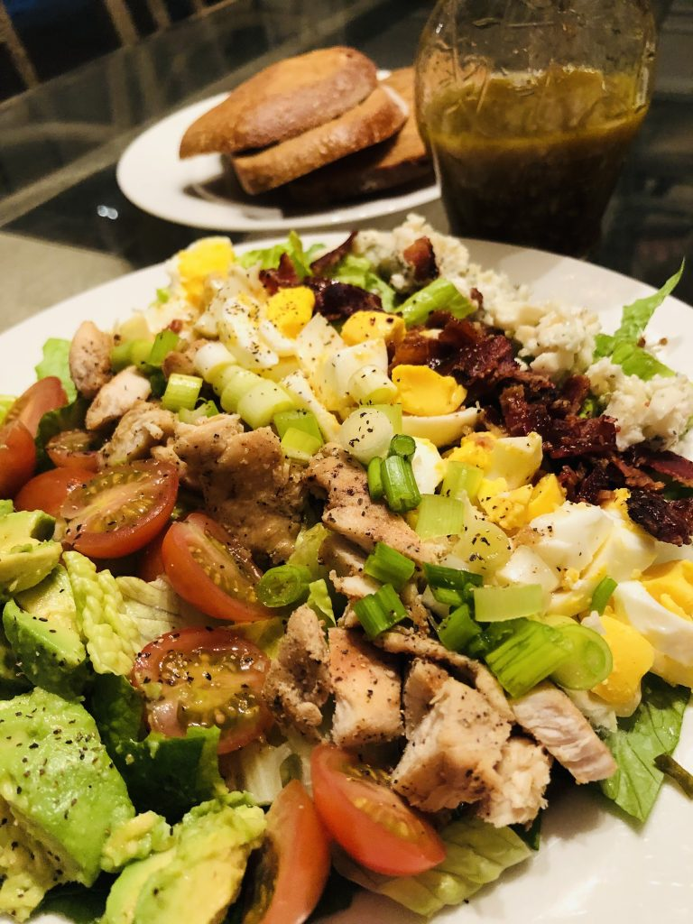 Cobb Salad on a white place with vinaigrette and slices of rye bread in the background